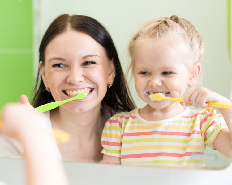 woman and child cleaning teeth