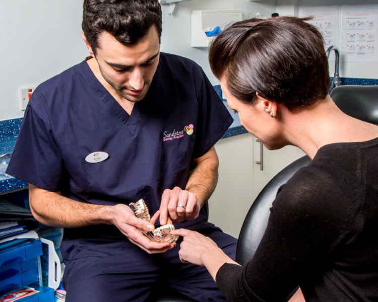 woman and dentist looking at teeth mould